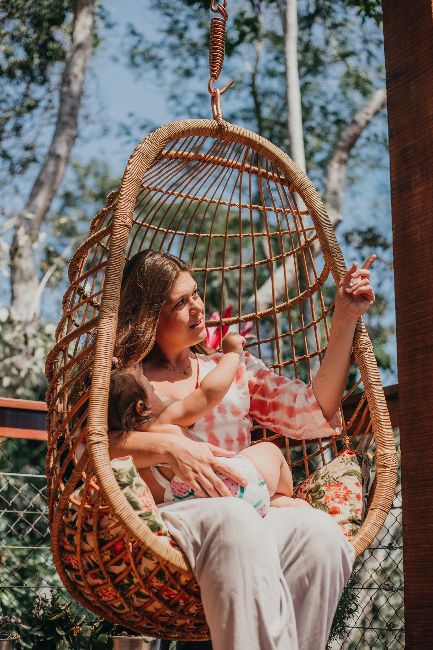girl in white and red dress sitting on brown woven hammock